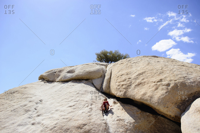 Boy crouching on rock mountain against sky during sunny day