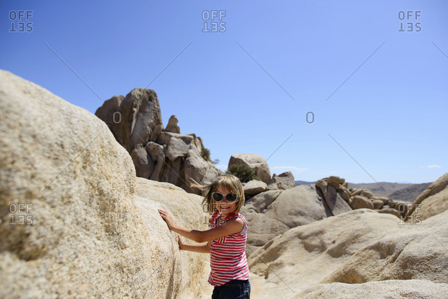 Portrait of girl standing by rocks at Joshua Tree National Park against clear sky during sunny day