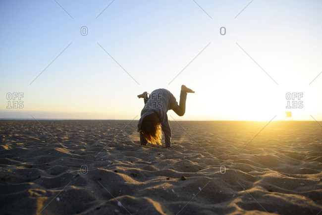 Girl practicing handstand at beach against clear sky during sunrise