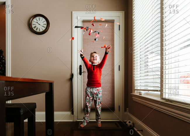 Happy boy throwing confetti while standing on doormat by door at home