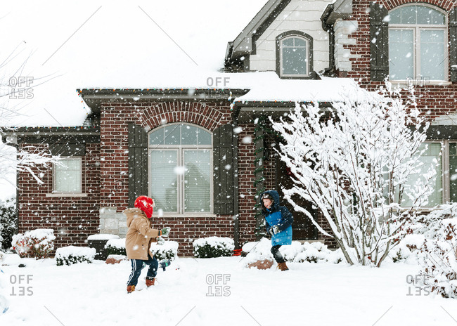 Happy brothers playing with snow in yard