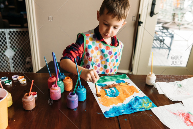 Boy painting picture on paper at table in house