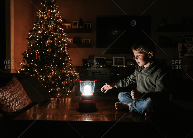 Boy with lantern sitting on table by Christmas tree at home