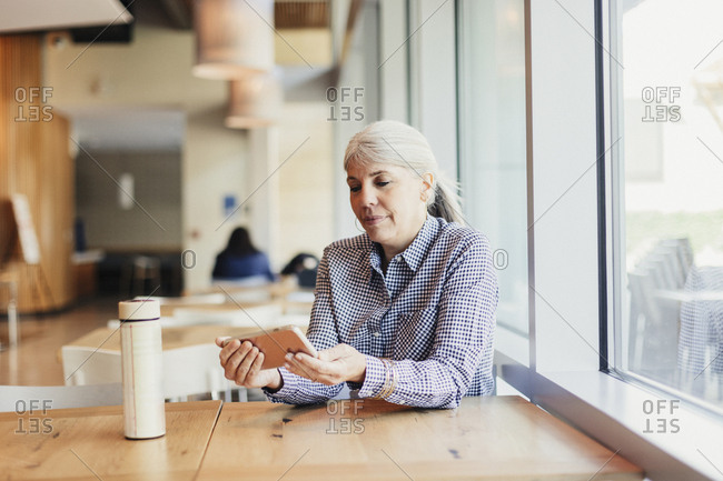 Businesswoman using mobile phone while sitting at office cafeteria