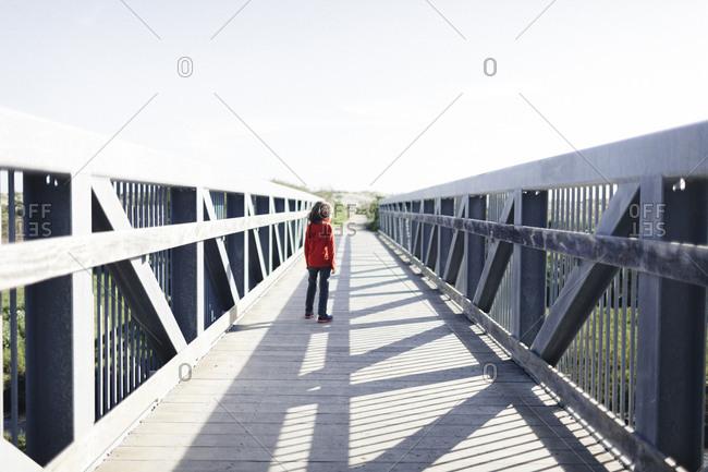 Rear view of boy standing on footbridge against clear sky during sunny day
