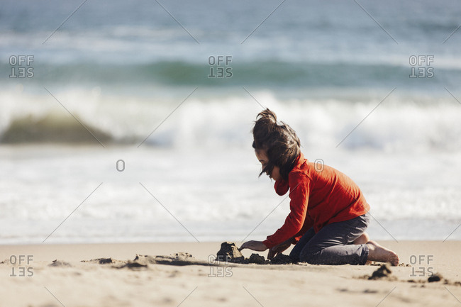 Side view of boy playing with sand at Limantour beach during sunny day
