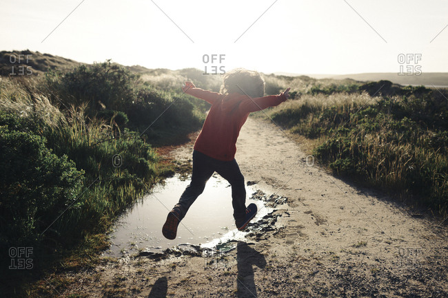 Rear view of boy with arms outstretched jumping over puddle on dirt road against clear sky