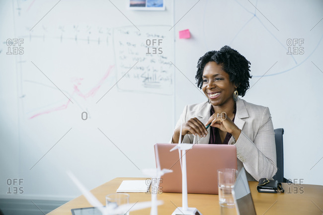 Smiling businesswoman looking away while sitting with laptop computer in board room