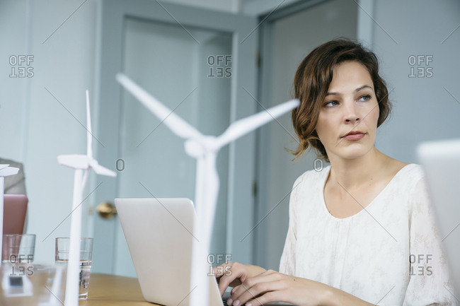 Businesswoman looking away while using laptop computer in office