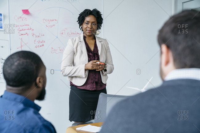 Businesswoman discussing with male colleagues during meeting in office