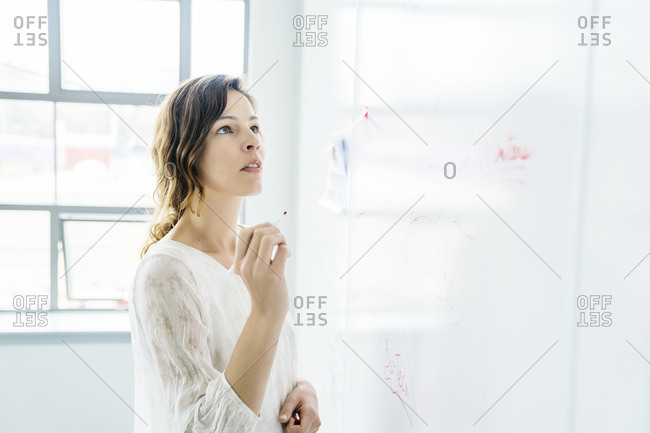 Side view of businesswoman writing on whiteboard in office