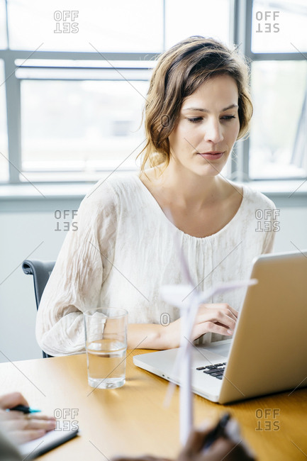 Businesswoman using laptop computer while working at desk in office