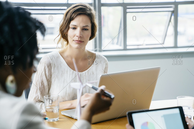 Businesswoman looking at colleague explaining wind turbine model in office