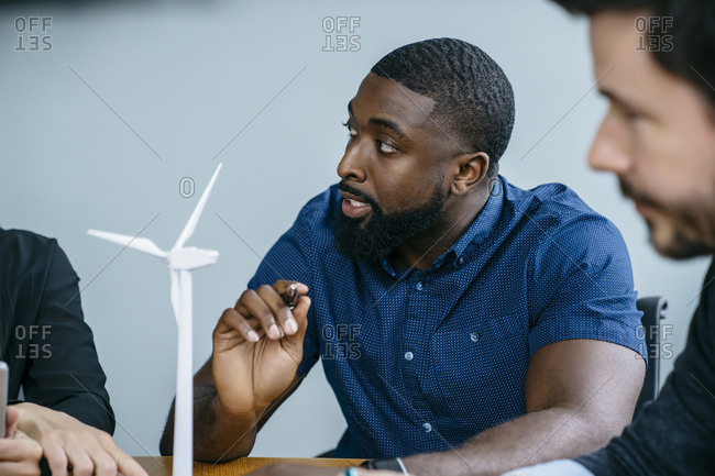 Business people working on wind turbine model during meeting in office