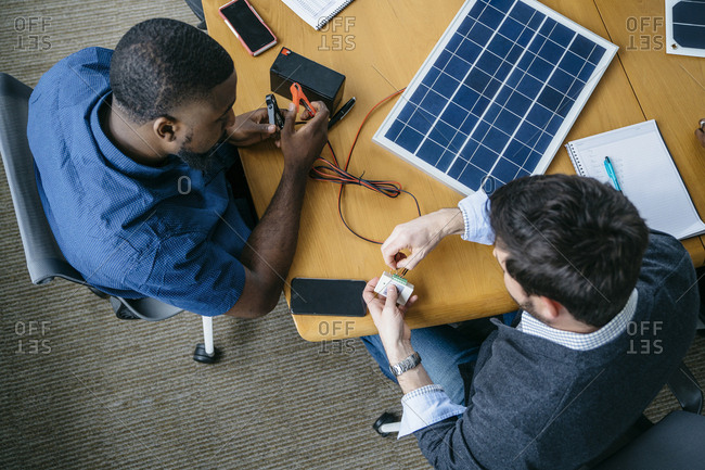 Overhead view of businessmen working on solar panel model in office
