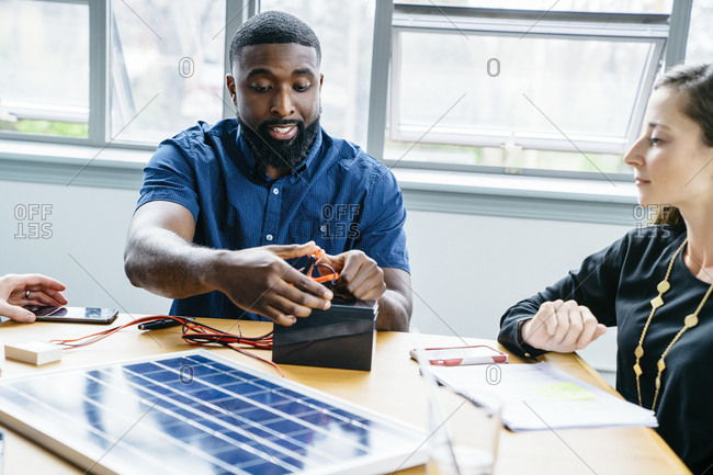 Businesswoman looking at colleague fixing metal clips on battery in office