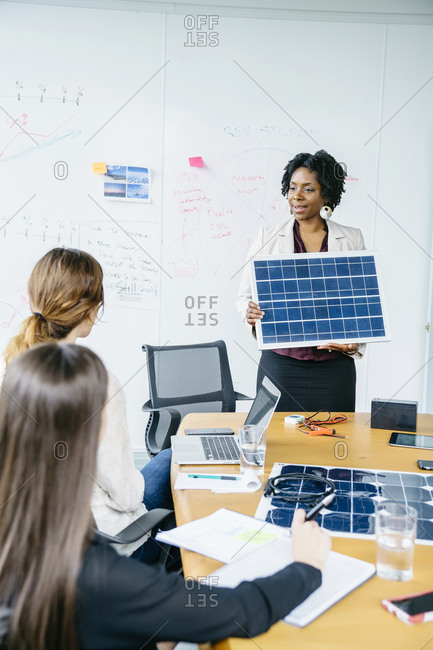 Businesswoman explaining solar panel model to female colleagues during meeting