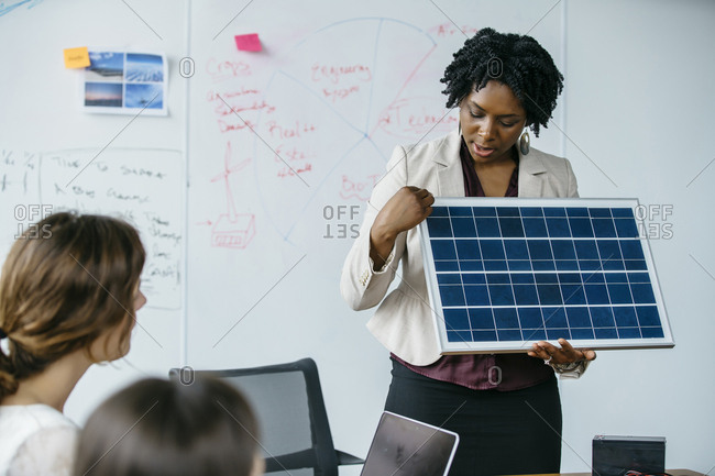 Businesswoman explaining solar panel model during meeting in office