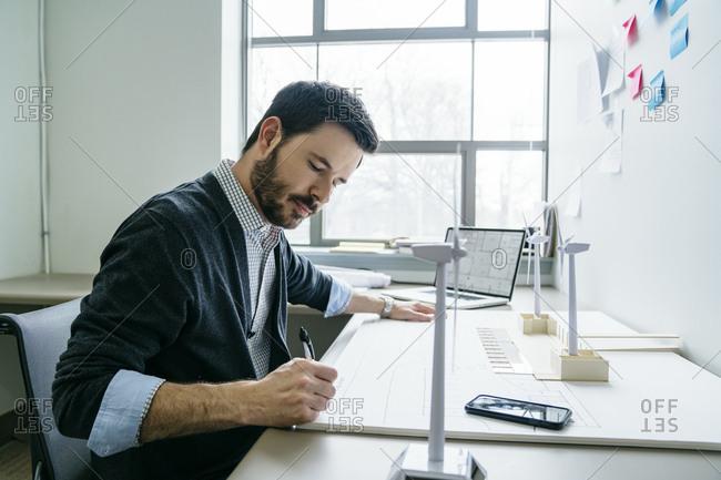 Businessman working on wind turbine models in office