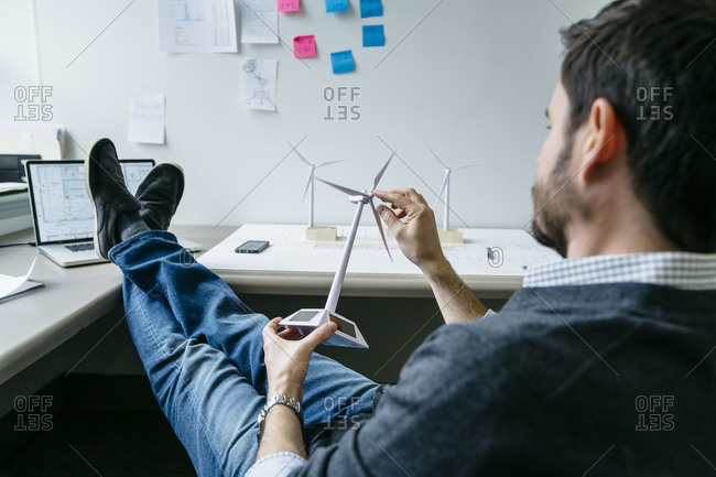 Businessman spinning windmill model while sitting in office