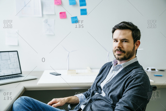 Portrait of confident businessman sitting on chair in office