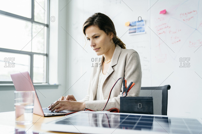 Businesswoman using laptop computer while sitting against whiteboard in office