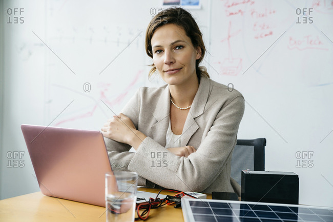 Portrait of businesswoman with arms crossed sitting against whiteboard in office