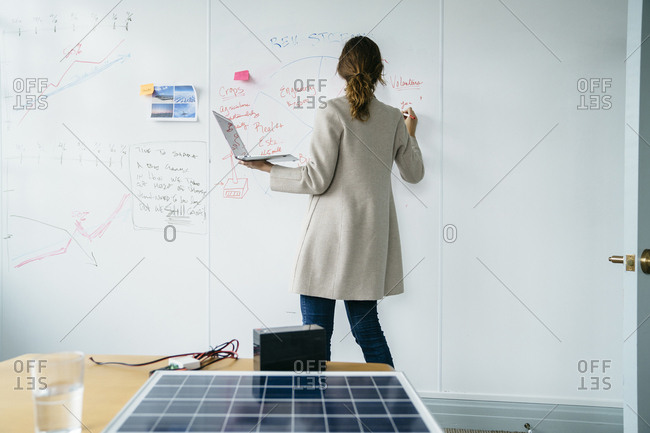 Rear view of businesswoman writing on whiteboard while working over solar panels in office