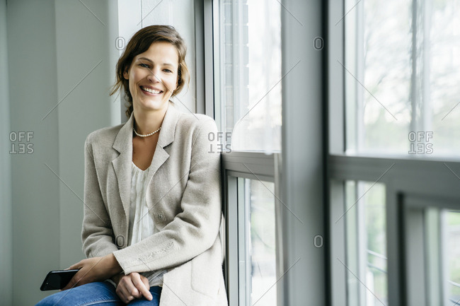 Portrait of smiling businesswoman sitting by window in office