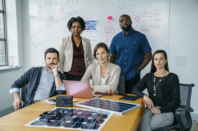 Portrait of business people by solar panel models on desk