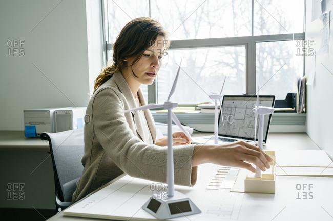 Side view of businesswoman arranging wind turbine models on desk
