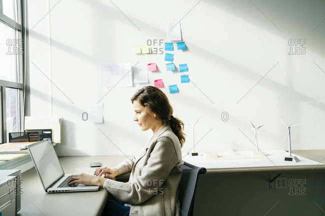Side view of businesswoman using laptop while working by wind turbine models arranged on desk