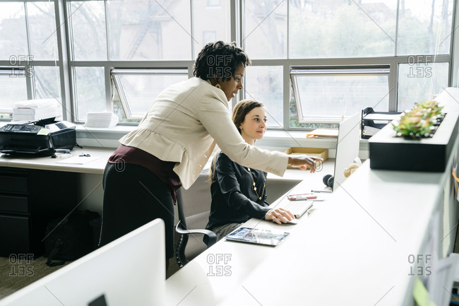 Businesswoman pointing on desktop computer while talking with colleague