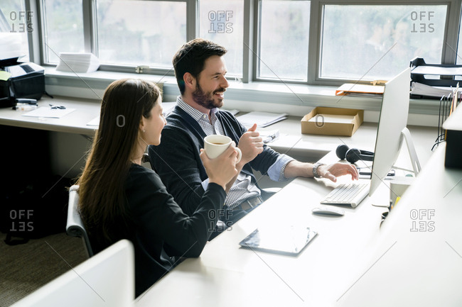 Smiling businessman using desktop computer while sitting with female colleague in office