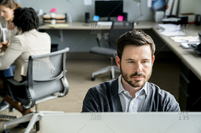 Businessman using desktop computer while colleagues discussing in background