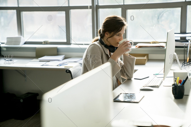 Side view of businesswoman having drink while working at desk in office