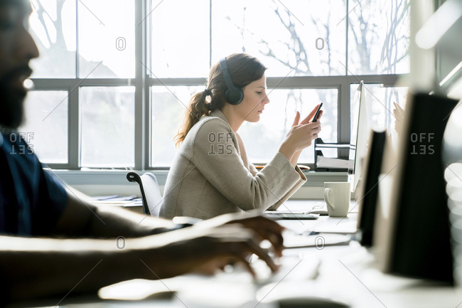 Businesswoman using smart phone while sitting by colleague in office