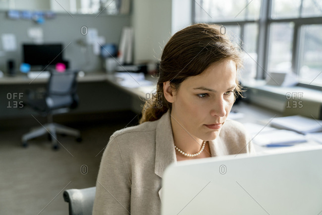 Businesswoman using desktop computer while sitting in office