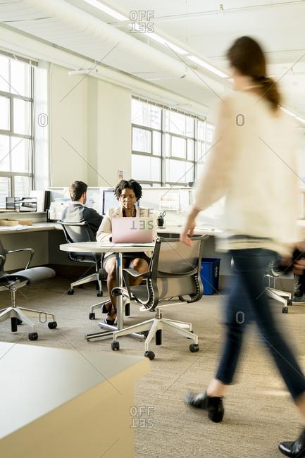 Blurred motion of businesswoman walking in office