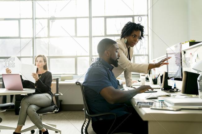 Businesswoman explaining to colleague using desktop computer