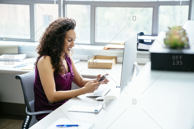 Smiling businesswoman using mobile phone while sitting at desk in office