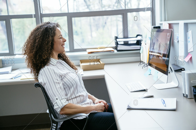 Side view of smiling businesswoman looking at desktop computer in office