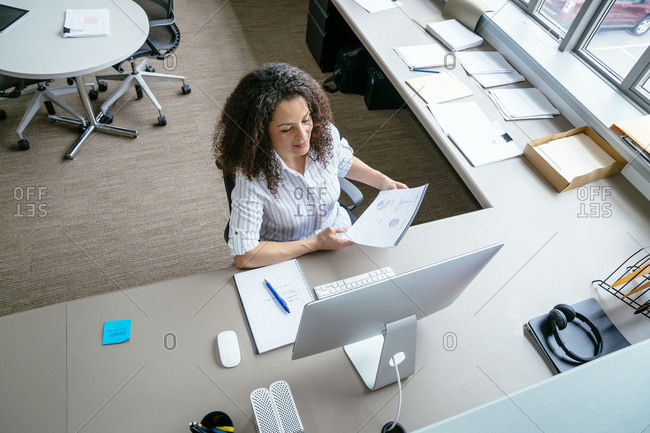 High angle view of businesswoman analyzing reports while sitting at desk in office