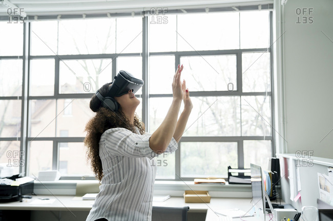 Businesswoman wearing virtual reality simulator in office