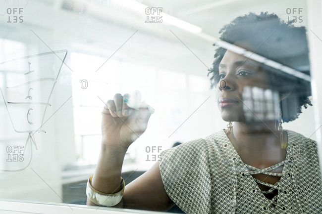 Businesswoman writing on window in office seen through glass