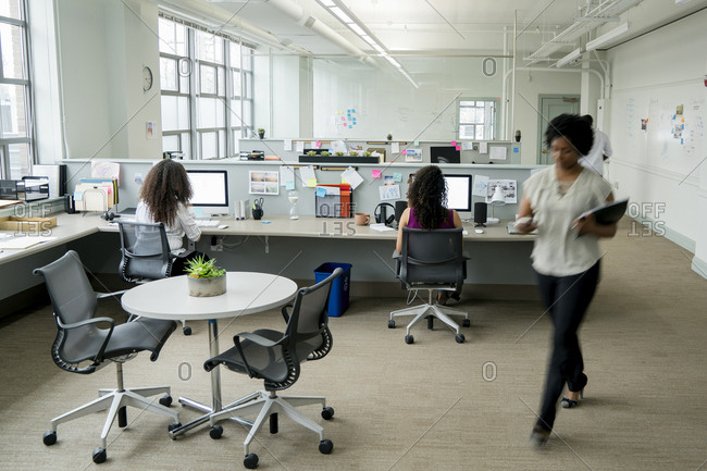 Businesswomen using desktop computer while sitting at desk in office