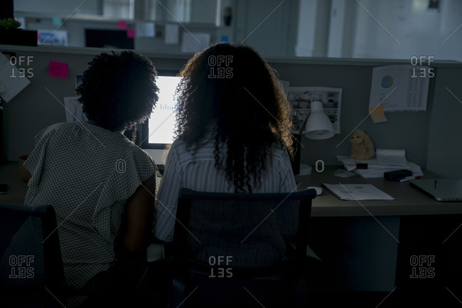 Rear view of female colleagues discussing while using desktop computer at desk in office