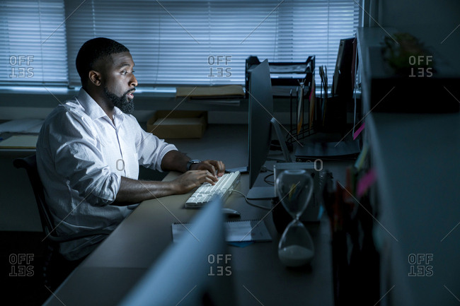 Businessman using desktop computer while sitting at desk in office