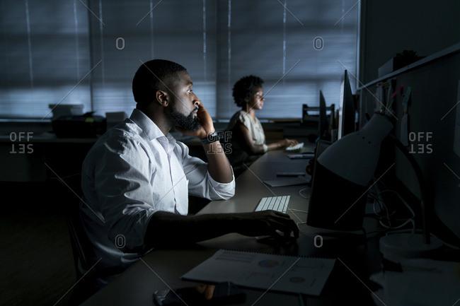 Colleagues working on desktop computers in office