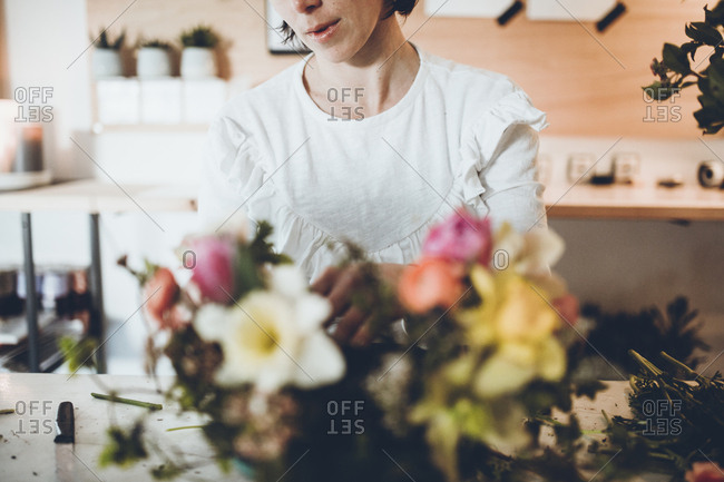 Midsection of florist arranging flowers at store